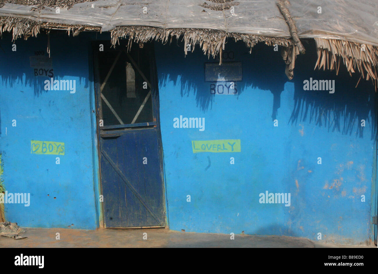 Blue village house with graffiti 'Boys Loverly' - Stock Image
