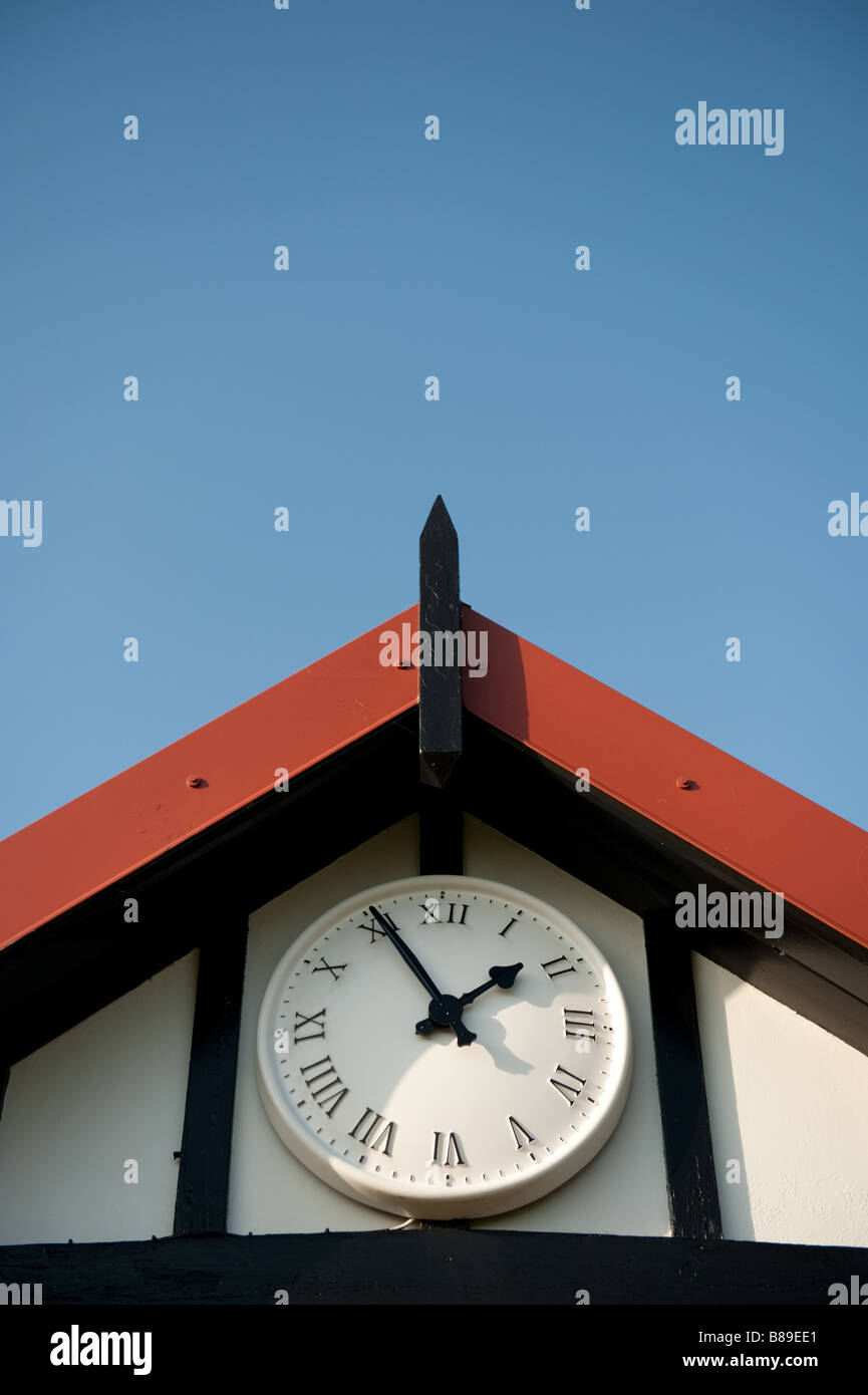 Clock on sports pavilion exterior set at five minutes to two 1 55pm - Stock Image