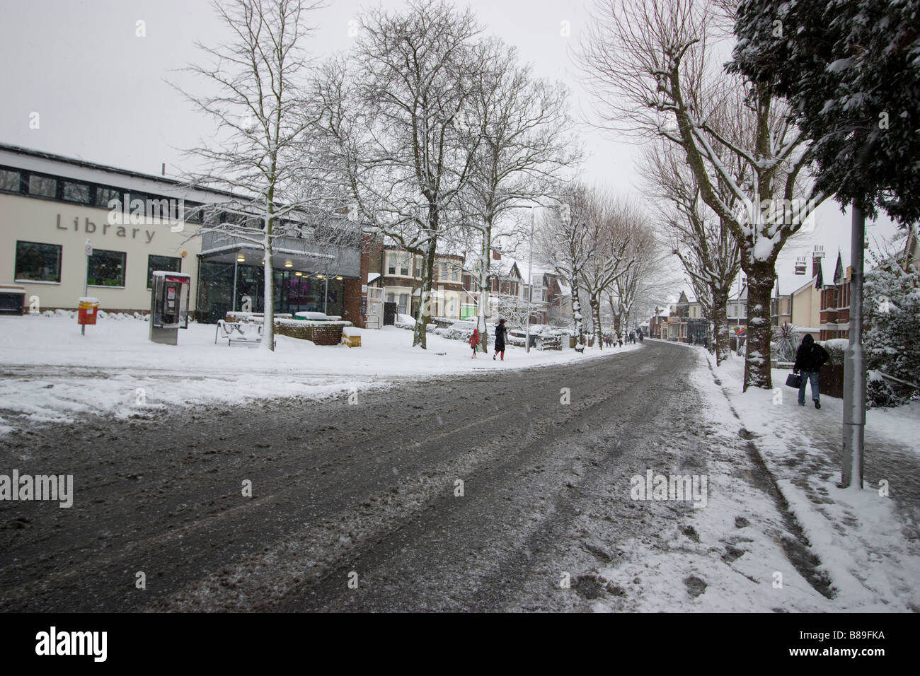 library Highams Park with snow and slush in road - Stock Image