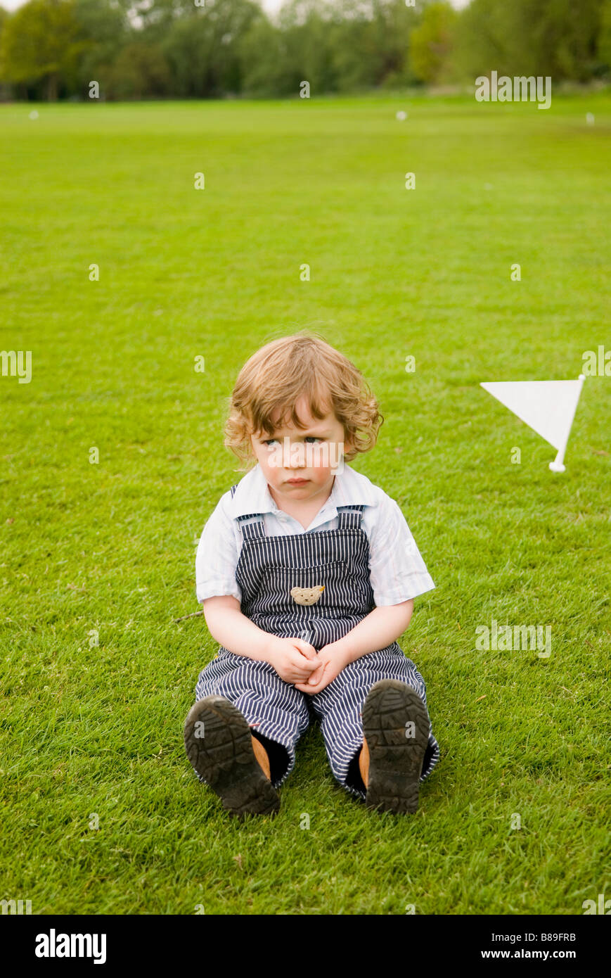 Young boy sitting on lawn - Stock Image