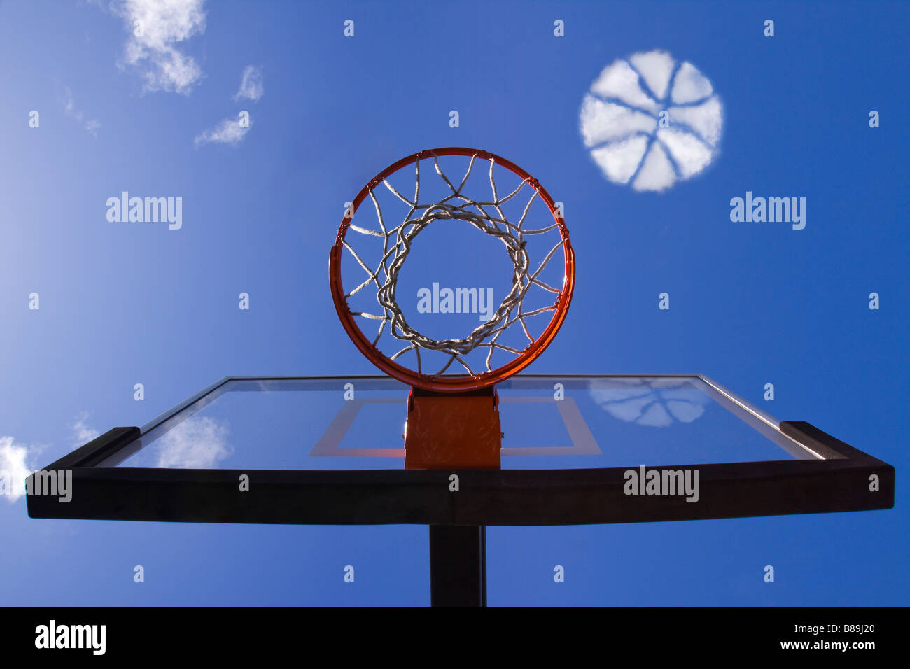 Cloud in the sky in the shape of a basketball approaching a basketball hoop as if it is about to go into the net - Stock Image