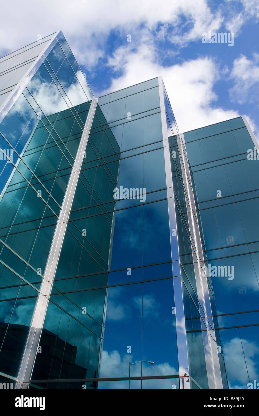 Three towers of a sleek modern glass office building with clouds and sky reflecting on the surface of the buildings - Stock Image