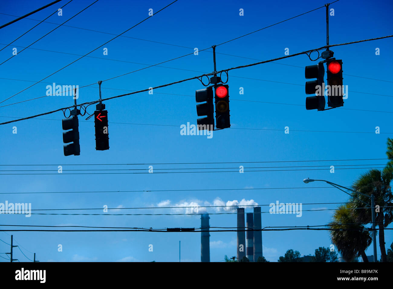 Traffic lights in the Tampa Bay area, Florida, US. The smoke stacks of the TECO power plant in the distance. - Stock Image