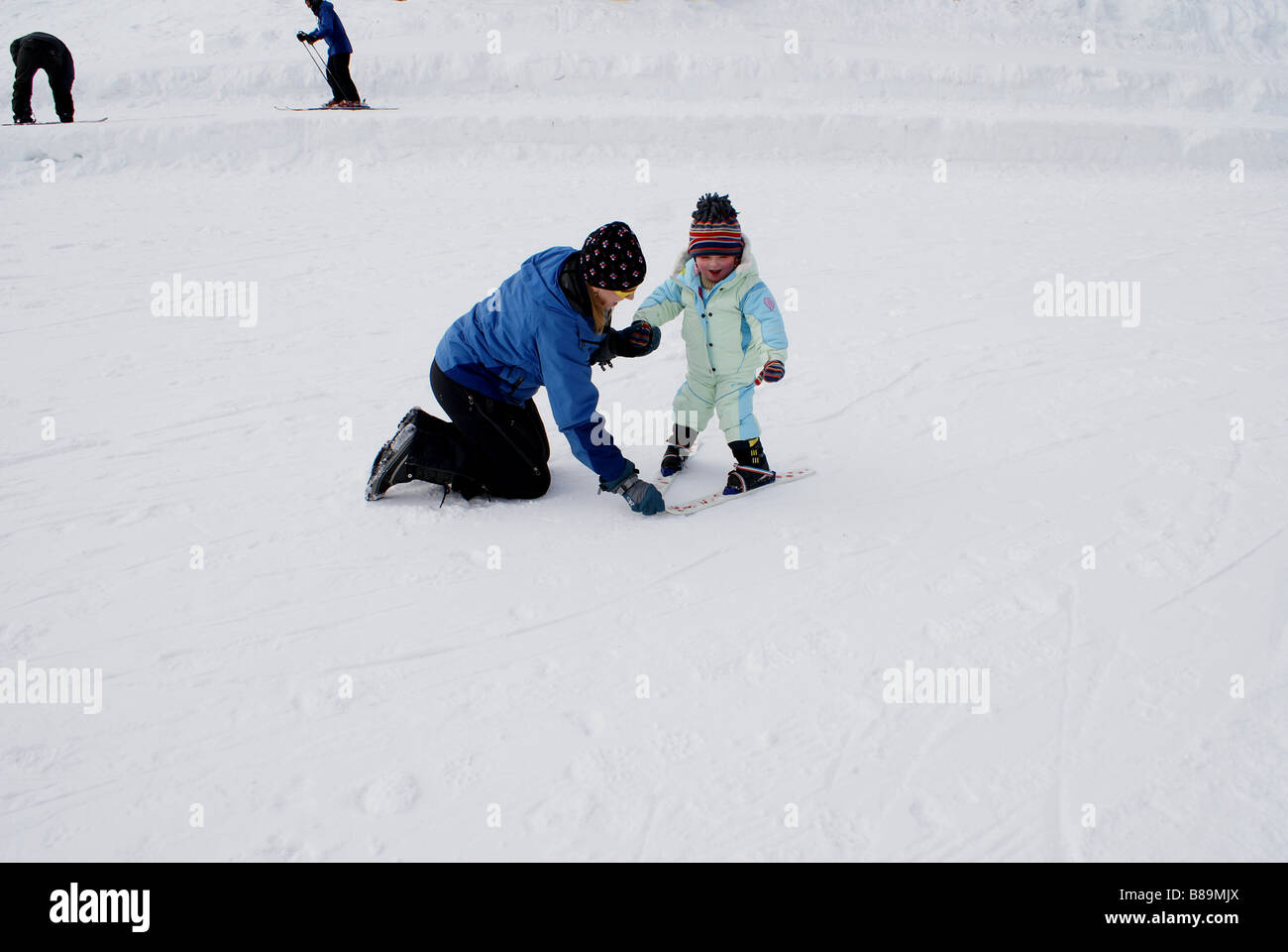 Ski instructor showing  2 year-old girl the snowplow position on beginner's slope at Snoqualmie Summit, Washington - Stock Image