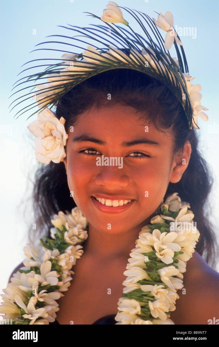 Polynesian girl with flower lei, headdress and beautiful smile on Cook Islands in South Pacific - Stock Image
