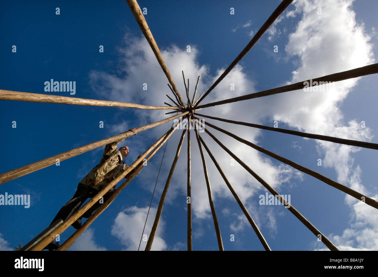 A man builds a tepee in a field in East Dean West Sussex - Stock Image