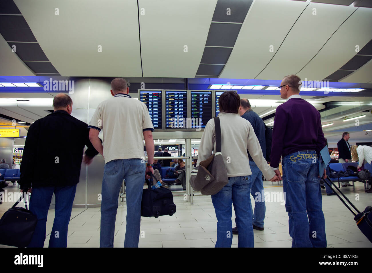 Travellers viewing departure and arrivals screen at Gatwick Airport - Stock Image
