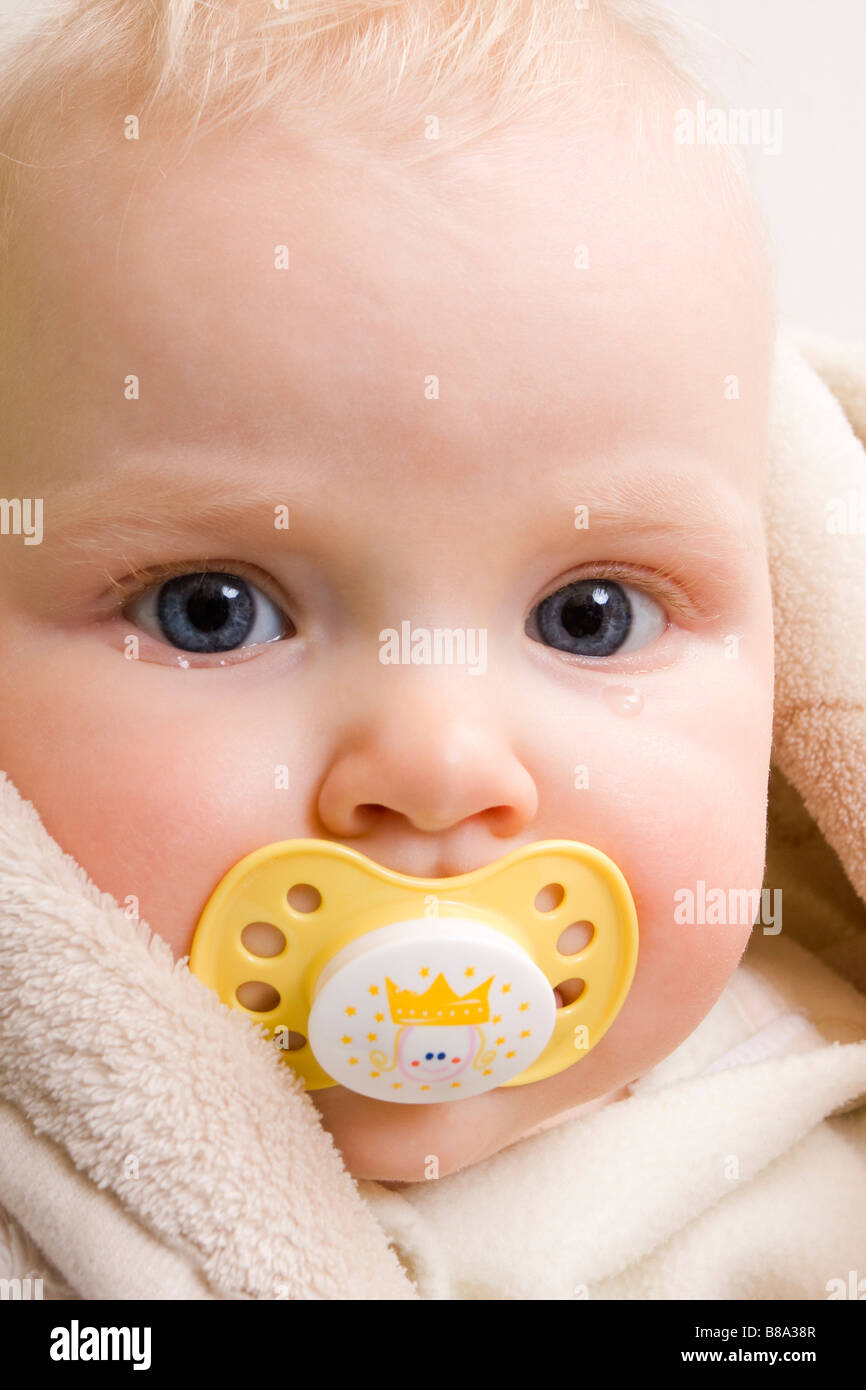 Suckling baby 7 months old with yellow dummy and with tear - Stock Image