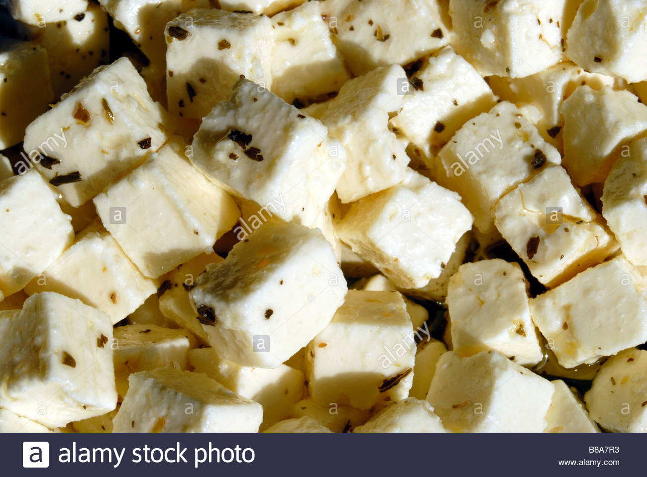 Blocks of Mediterreanean style cheese in oil and herbs. - Stock Image