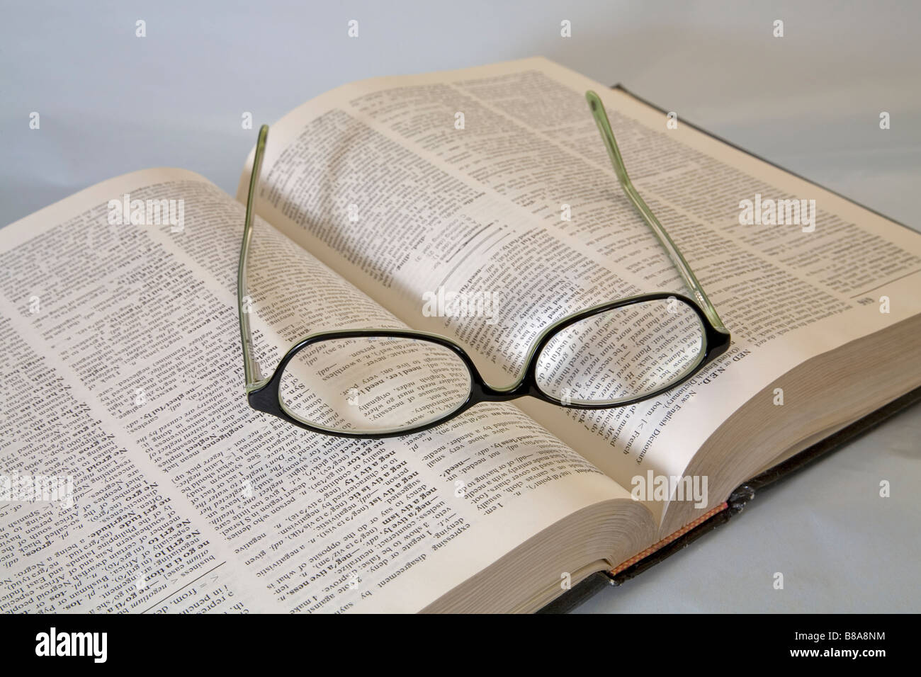 A pair of common reading eye glasses or spectacles lying on an open dictionary - Stock Image