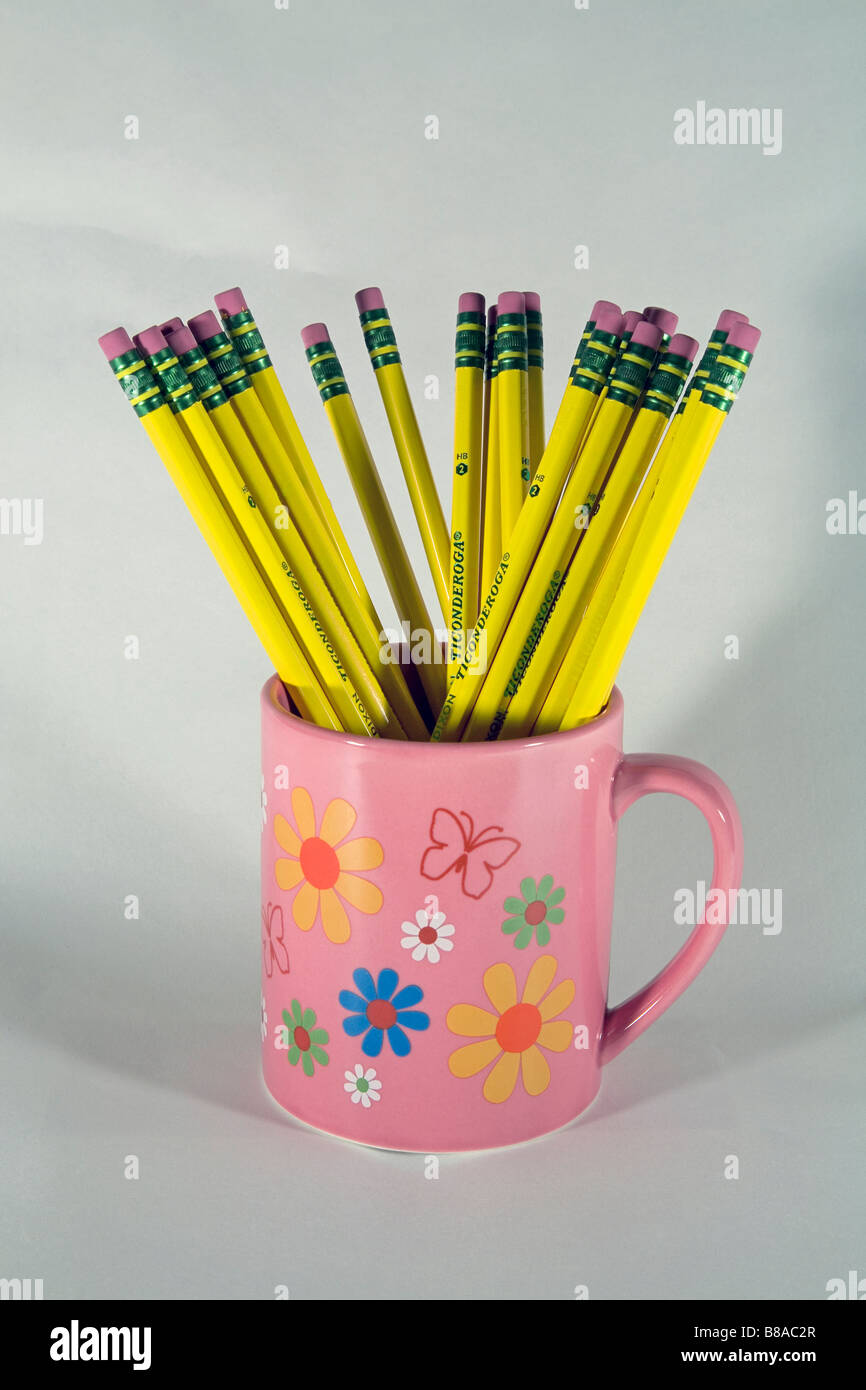 A cup or mug of Number 2 Ticonderoga lead or graphite yellow pencils and erasers - Stock Image