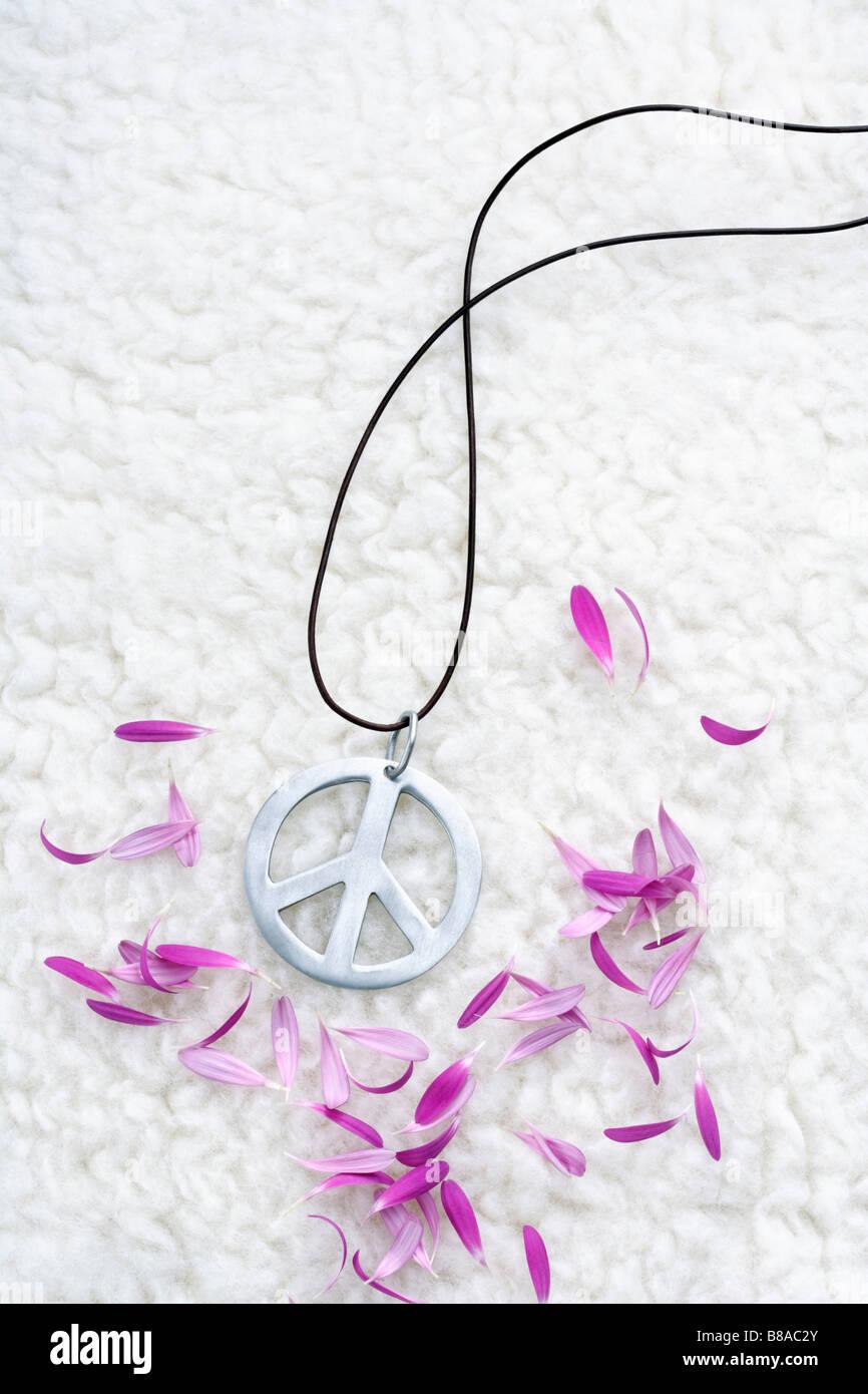 Peace Zeichen und Bluetenblaetter auf Flokati - Stock Image