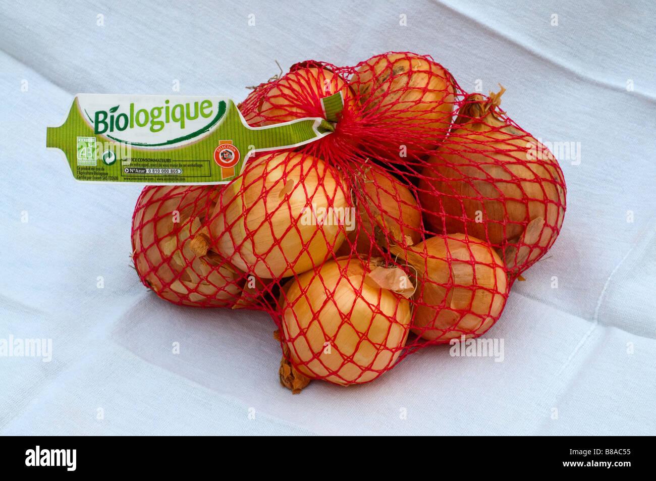 1 kilo sack / net of French Organic / Biologique onions. - Stock Image