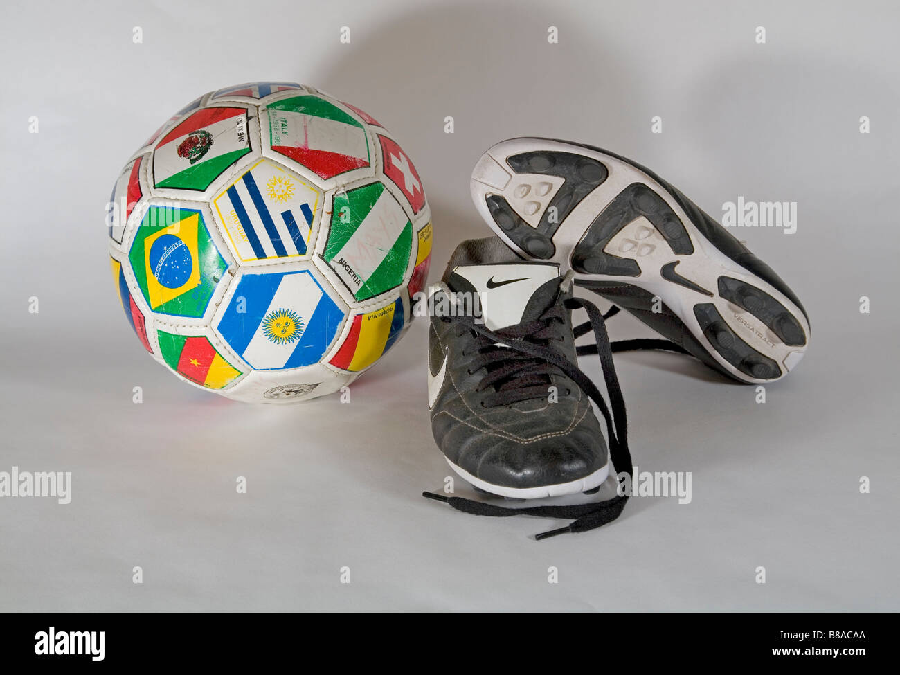 Old very used soccer football shoes and a soccer ball - Stock Image
