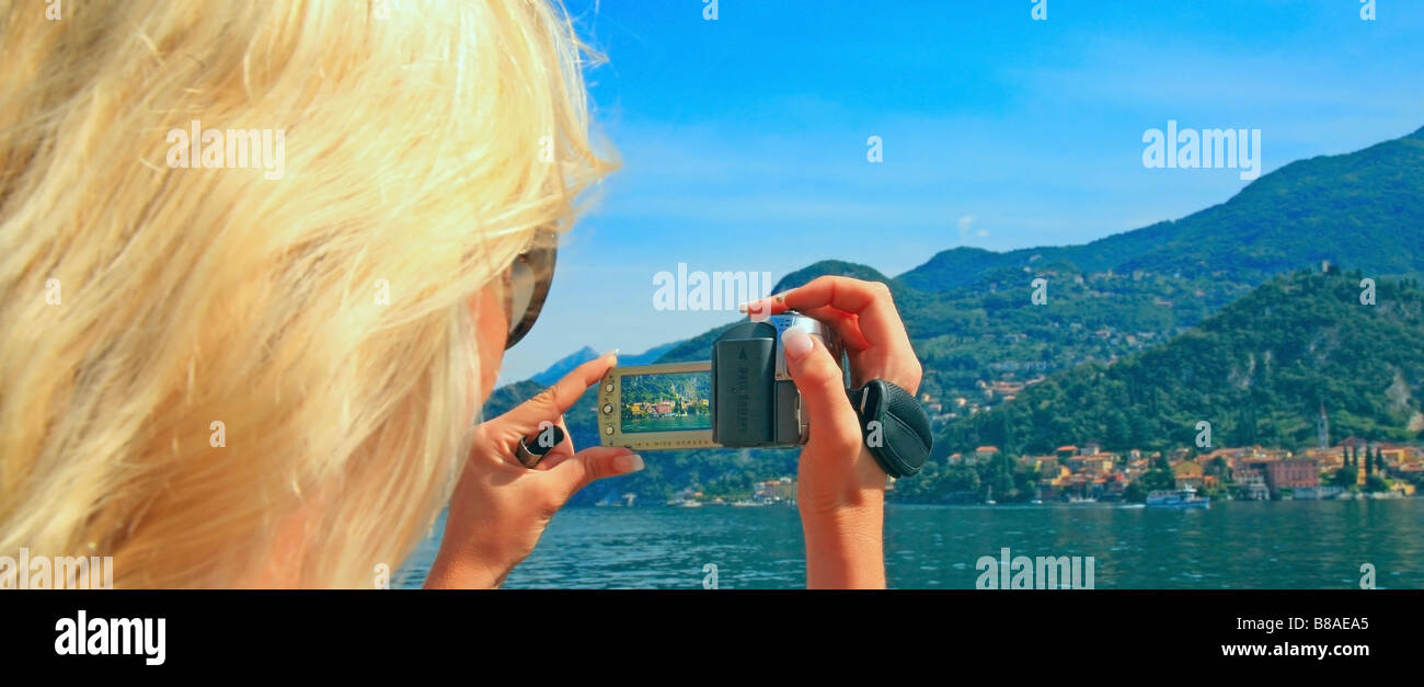 Young woman taking photograph from a passenger ferry crossing from Bellagio to Varenna on Lake Como Stock Photo