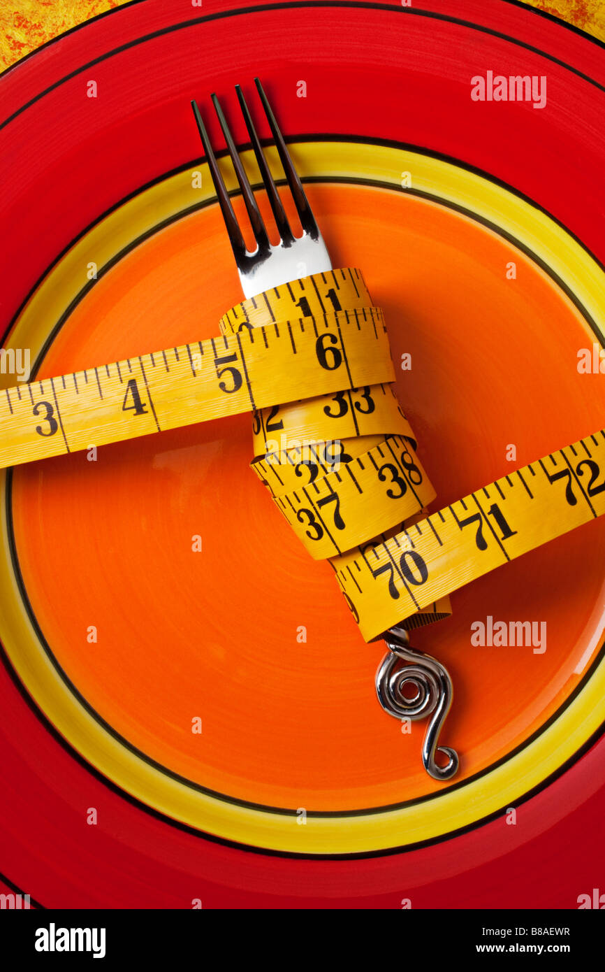 Tape measure wrapped around fork on plate - Stock Image