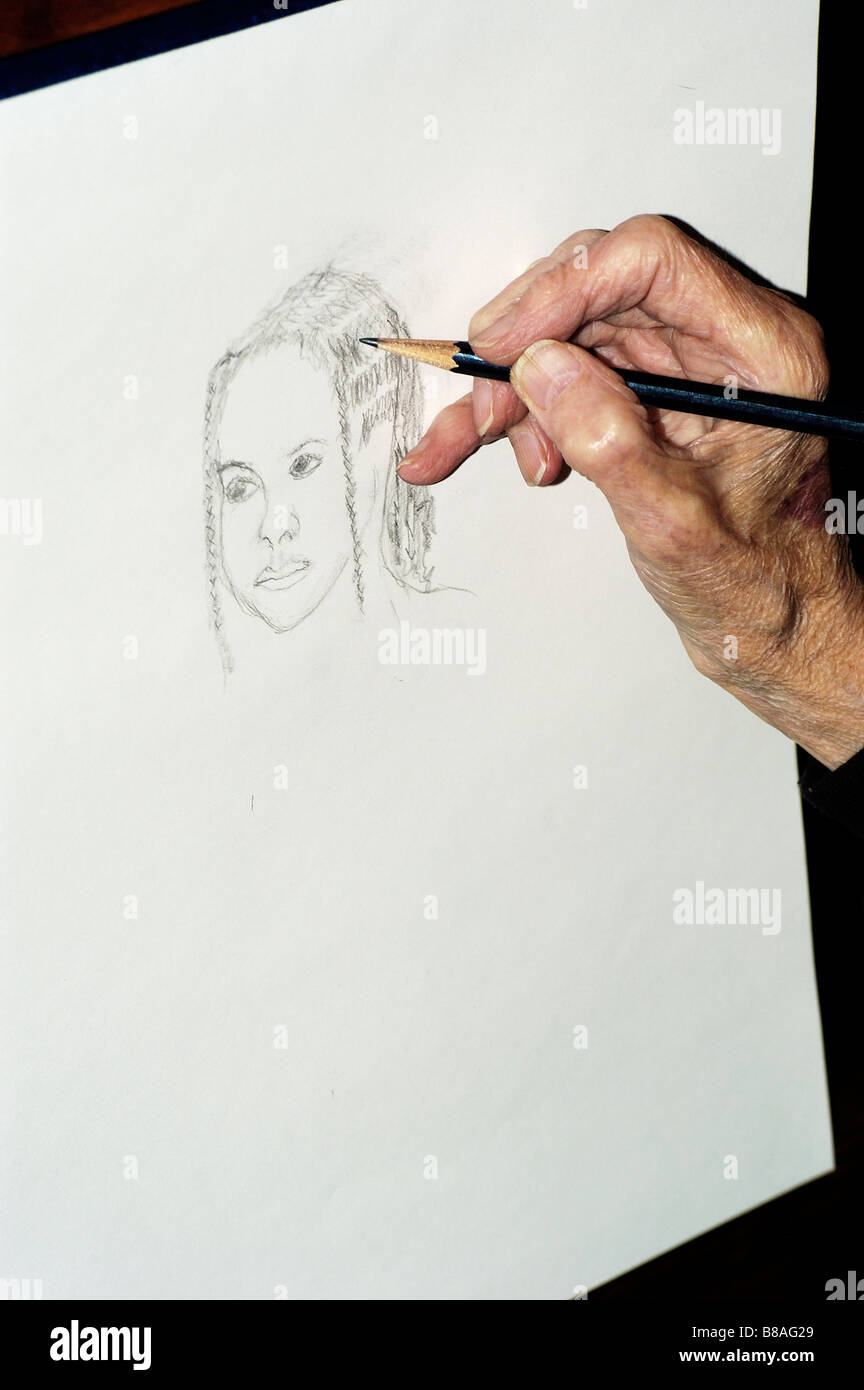 an elderly woman s hand drawing a picture of a young woman stock