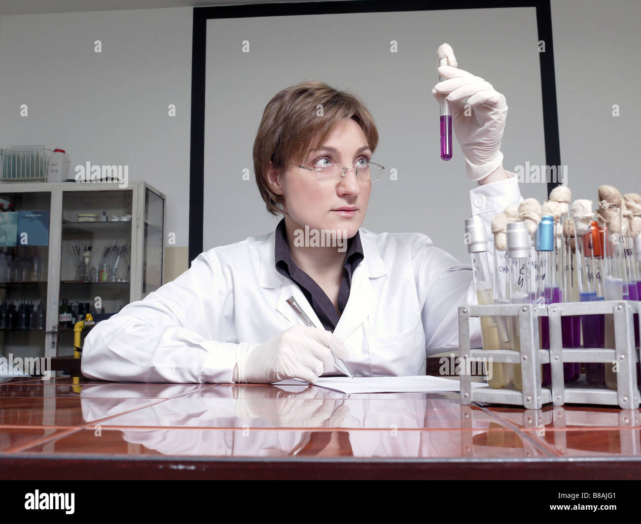 Female laboratory technician sitting behind laboratory desk looking at specimen taking observation notes - Stock Image