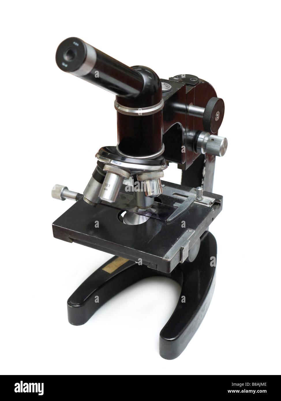 Old monocular microscope shot over white background - Stock Image