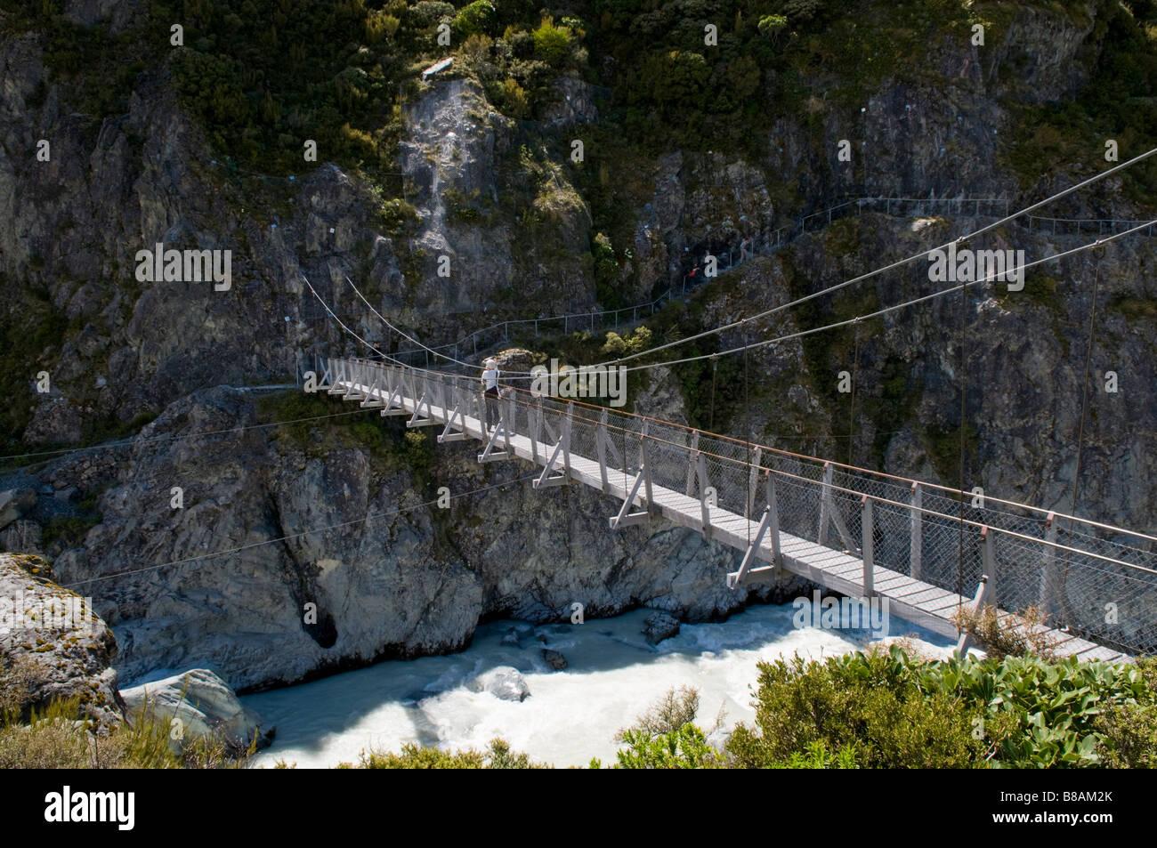 Upper footbridge over the Hooker River - tourists crossing - Stock Image