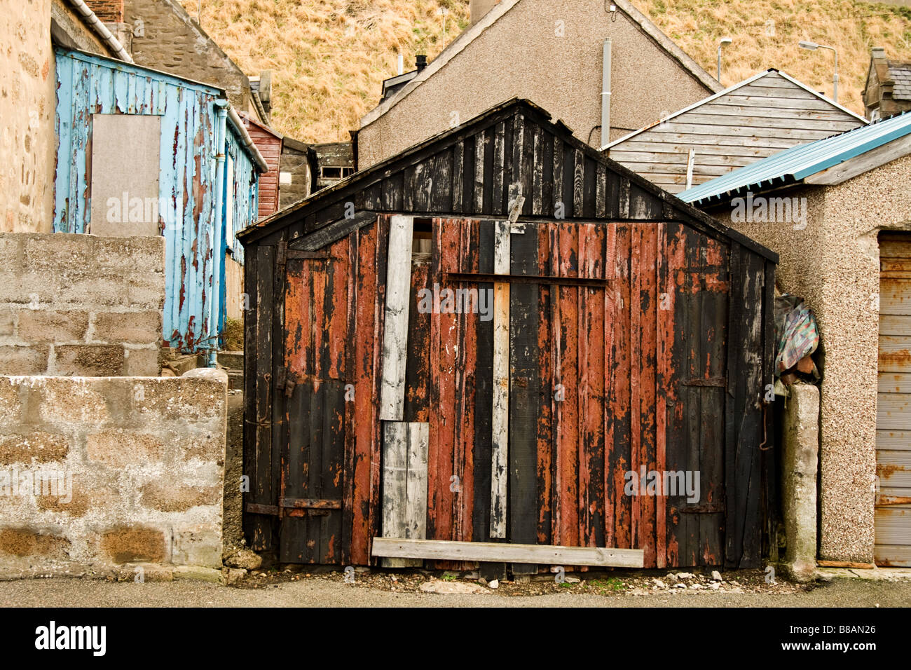 Old weatherbeaten red and black shack slightly squint in Buckie, Scotland - Stock Image