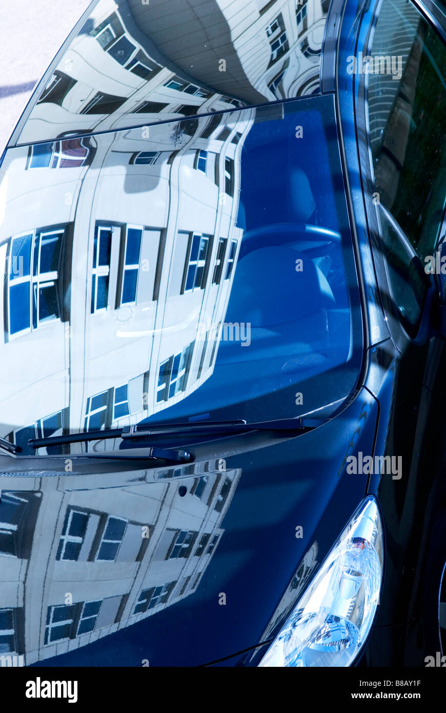 detail of polished car reflecting office blocks in its windows and body work - Stock Image