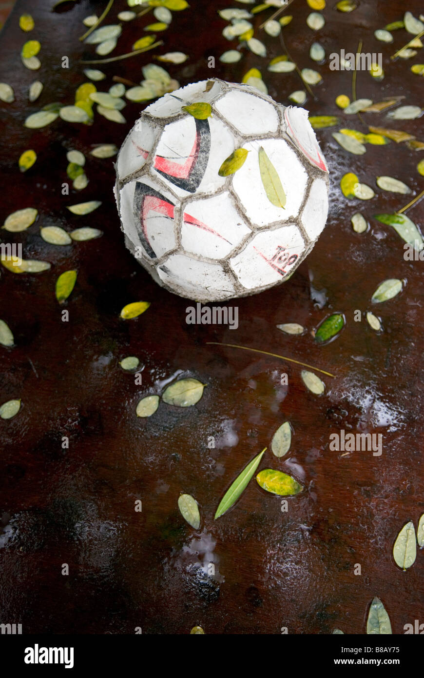a well worn used deflated football in the rain on a table surrounded by fallen leaves - Stock Image