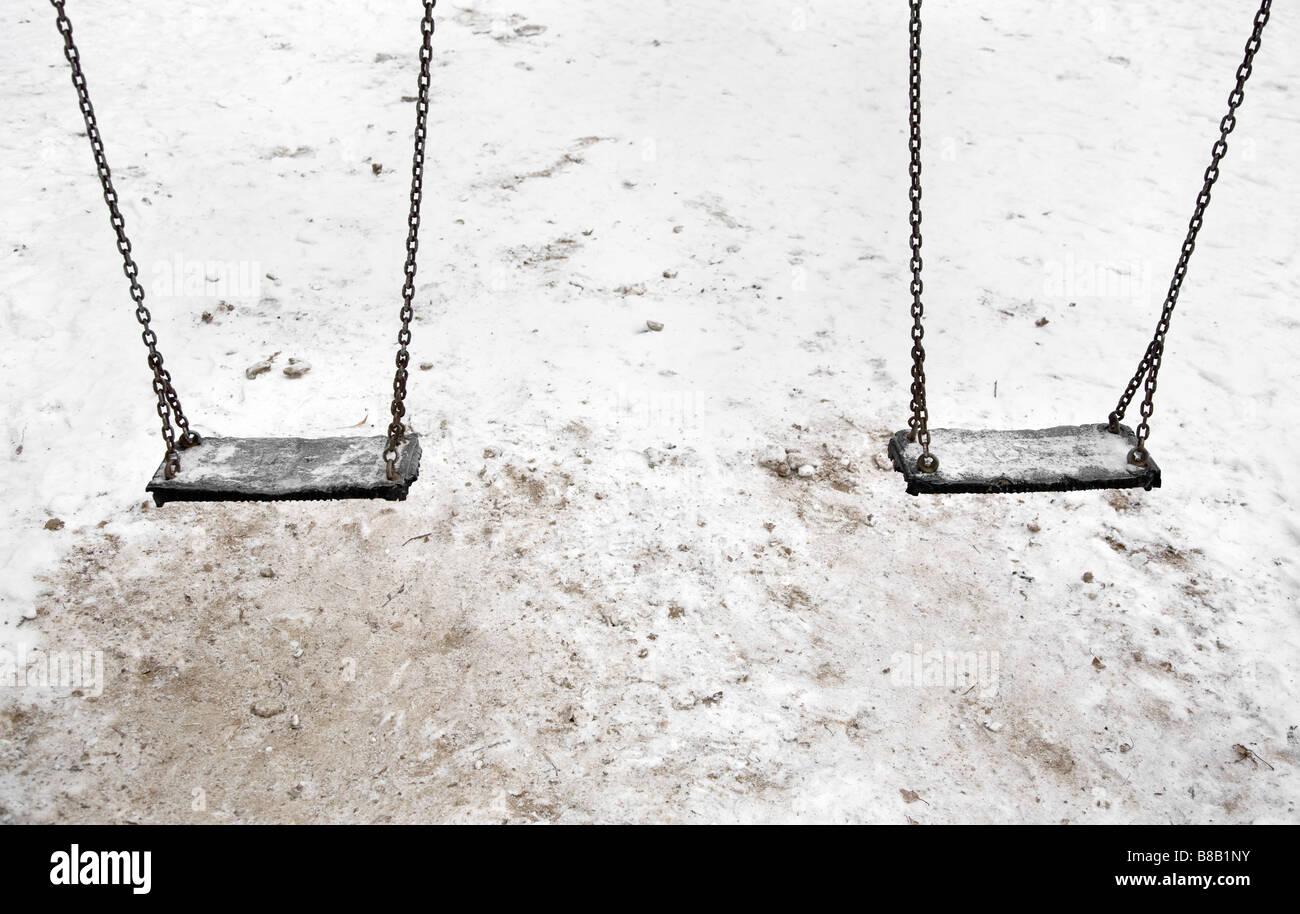 empty swings in winter - Stock Image
