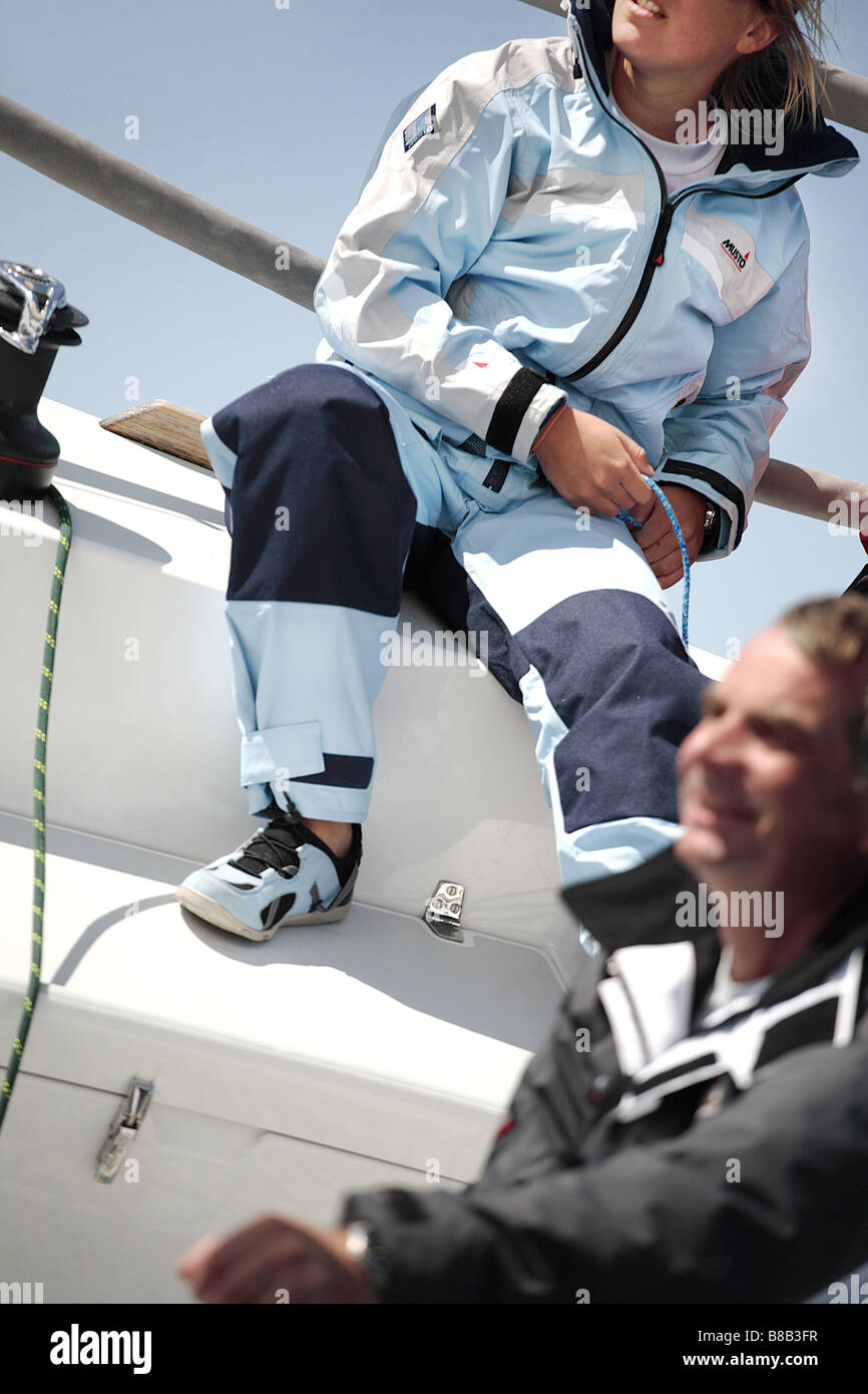 2 sailors one male one female crewing a yacht. The image is color and in portrait format. - Stock Image