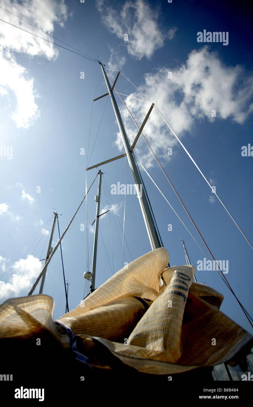 Color portrait format of a yacht and it sails shot against a blue sky. - Stock Image