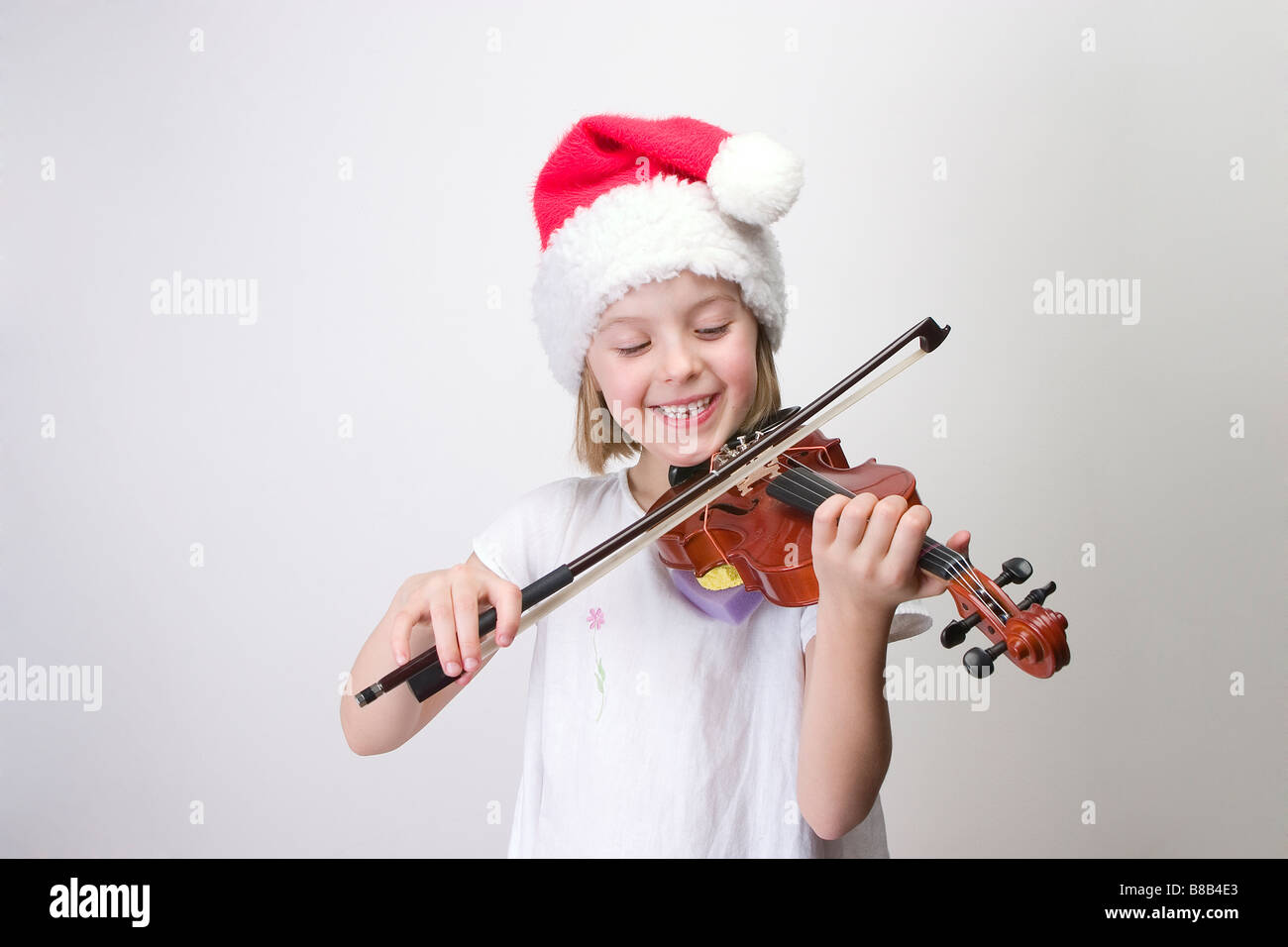 Girl - 6 years old  playing violin in Santa hat - Stock Image