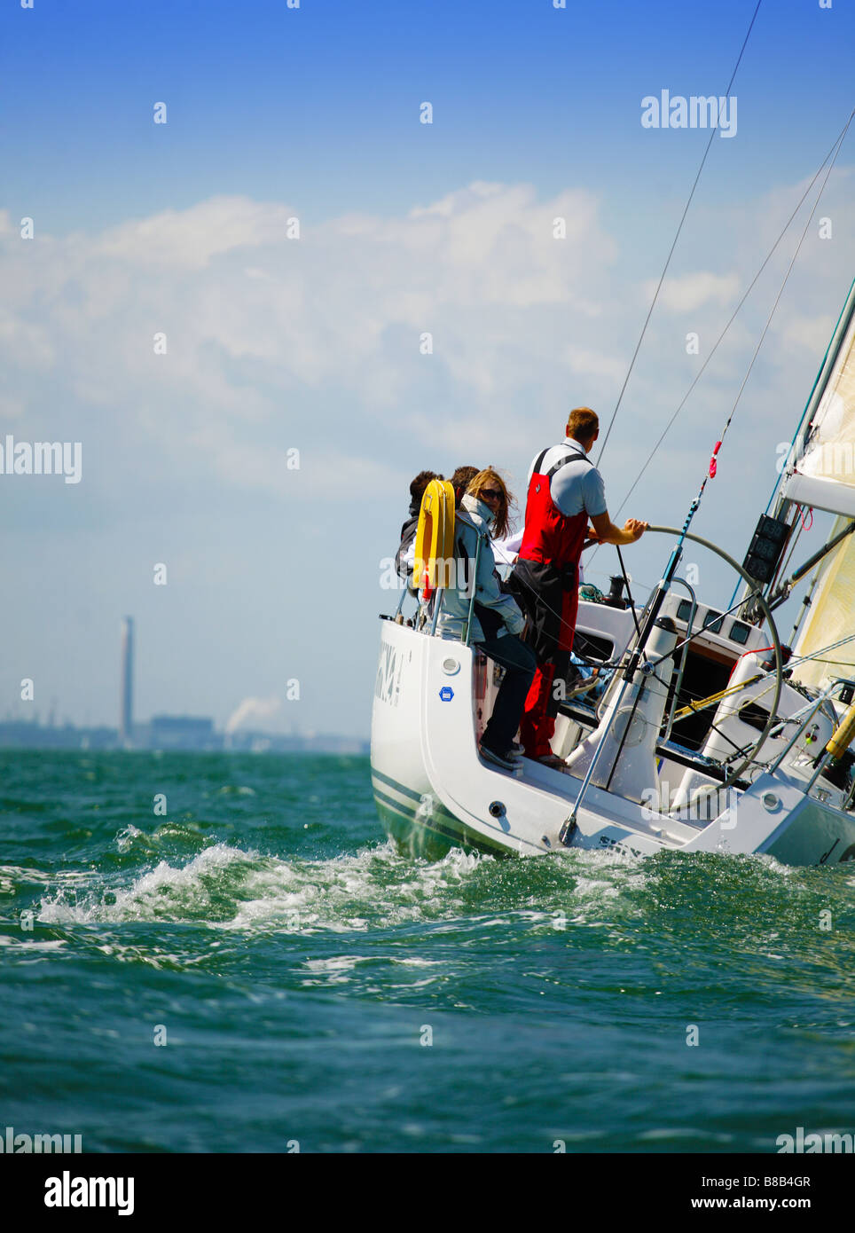 Image of a yacht sailing on the Solent,England. It features the crew and is a back view of the yacht. - Stock Image