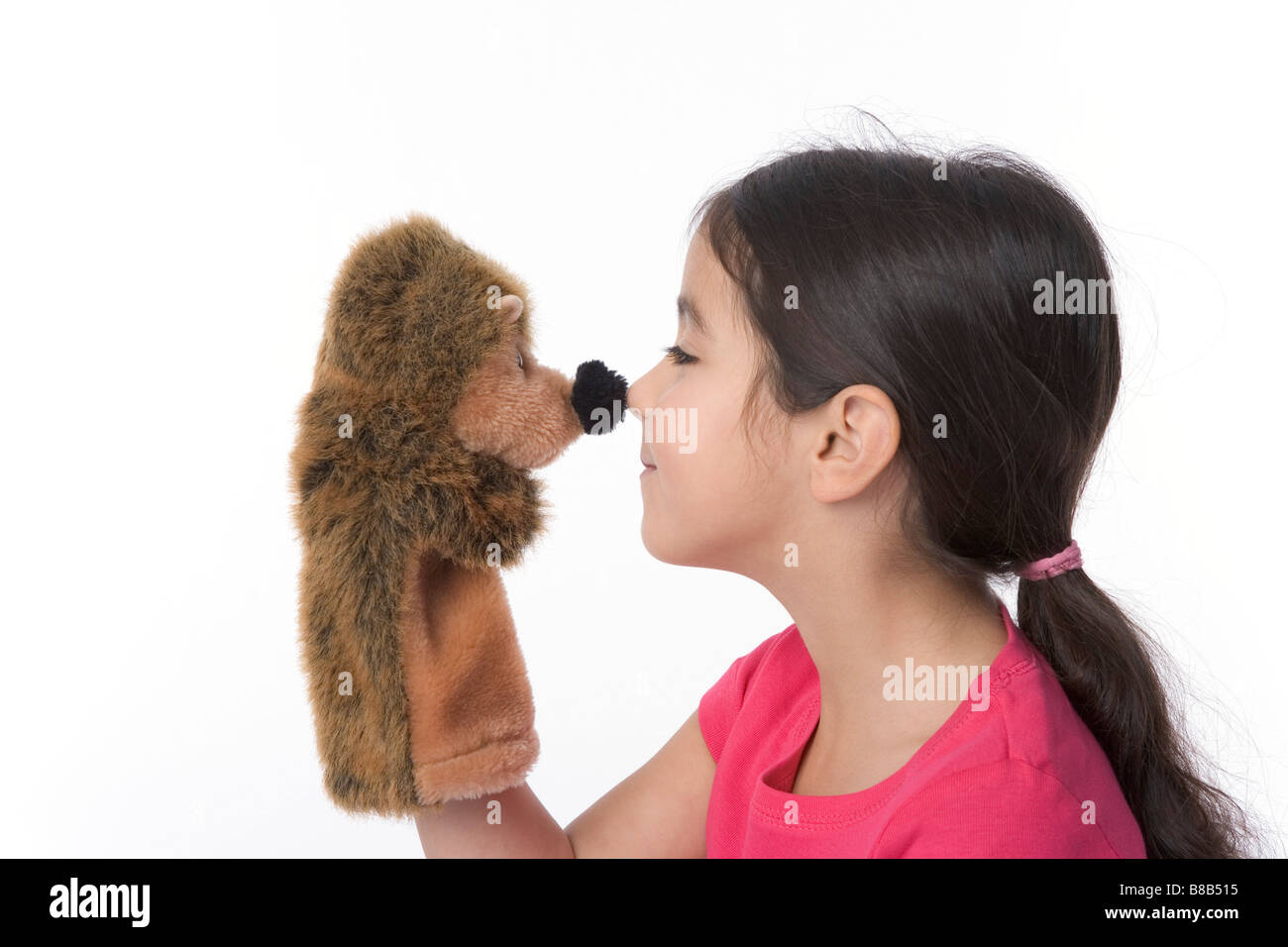 Little girl with hedgehog glove puppet - Stock Image