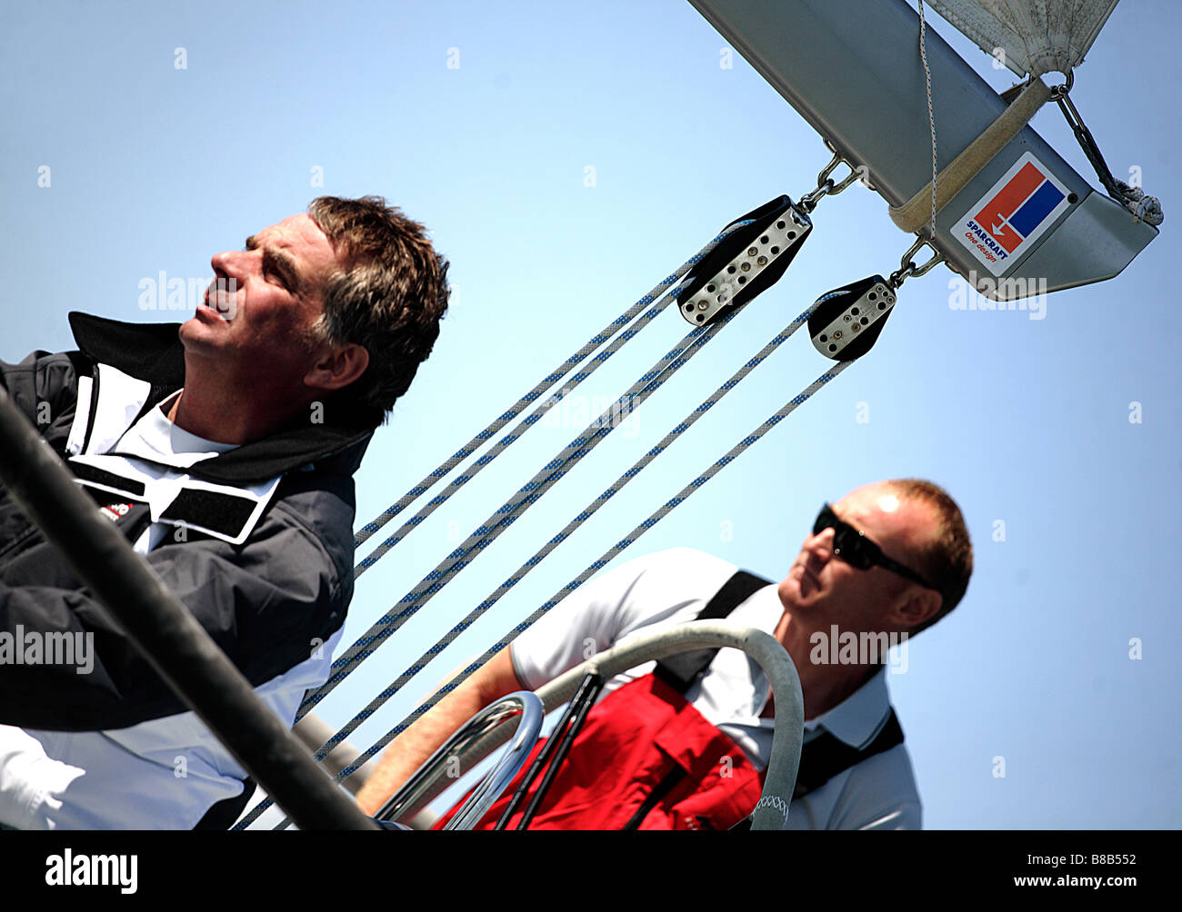 2 men,European,white sailing a yacht,it features rigging and is shot at a lw angle. - Stock Image