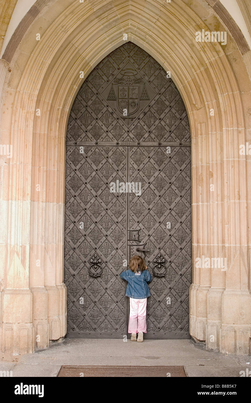 Girl - 5 years old in front of a big church door, Wroclaw, Poland - Stock Image