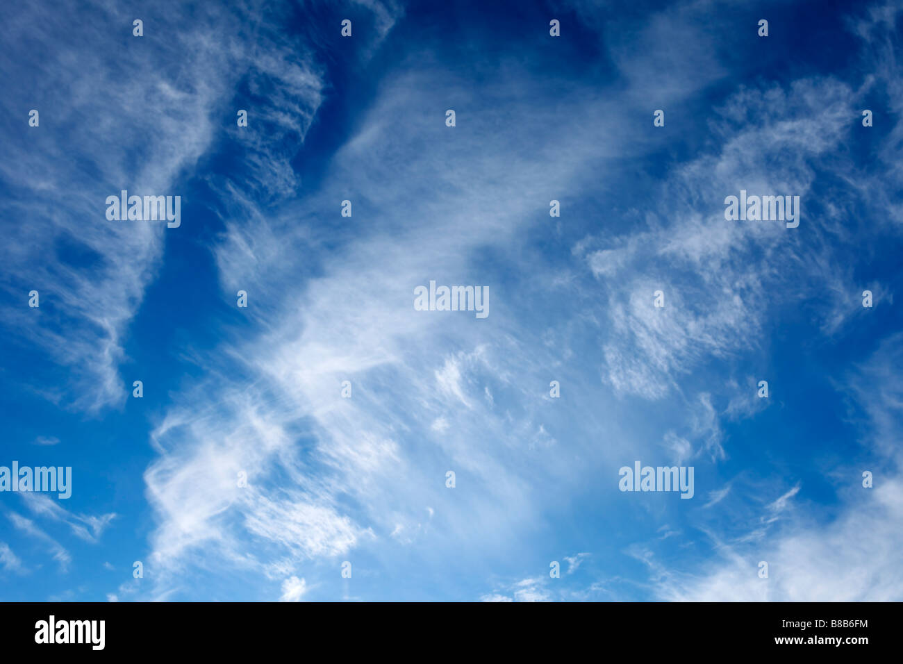 Blue sky with white wispy clouds - Stock Image