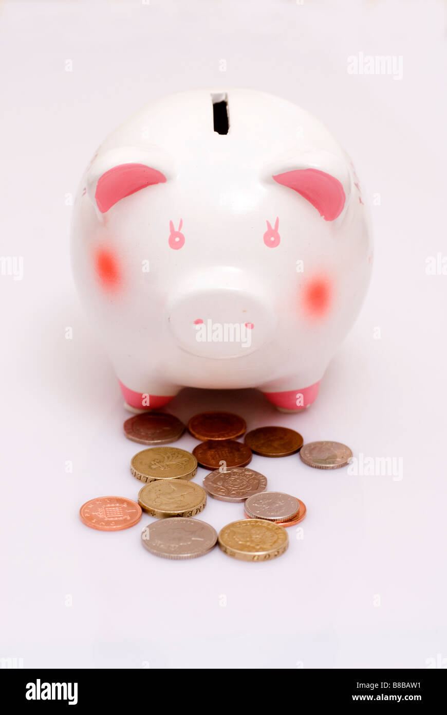 British coins out of a piggy bank on a white background - Stock Image
