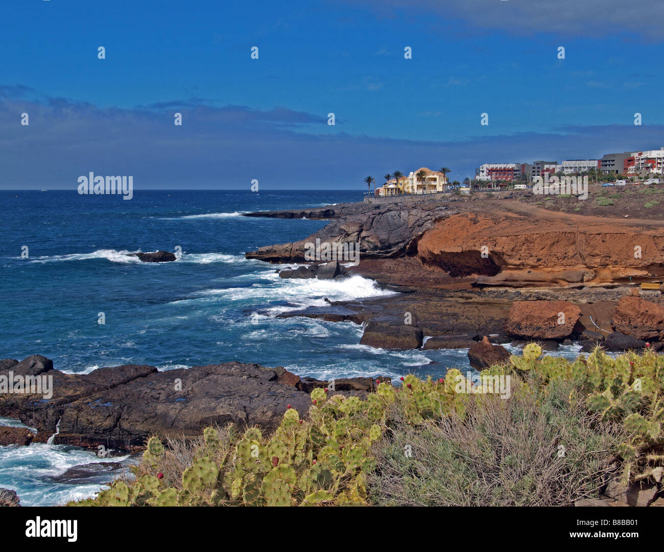 Sea braking on the volcanic rock coastline in Tenerife with houses on the top of the cliff. - Stock Image