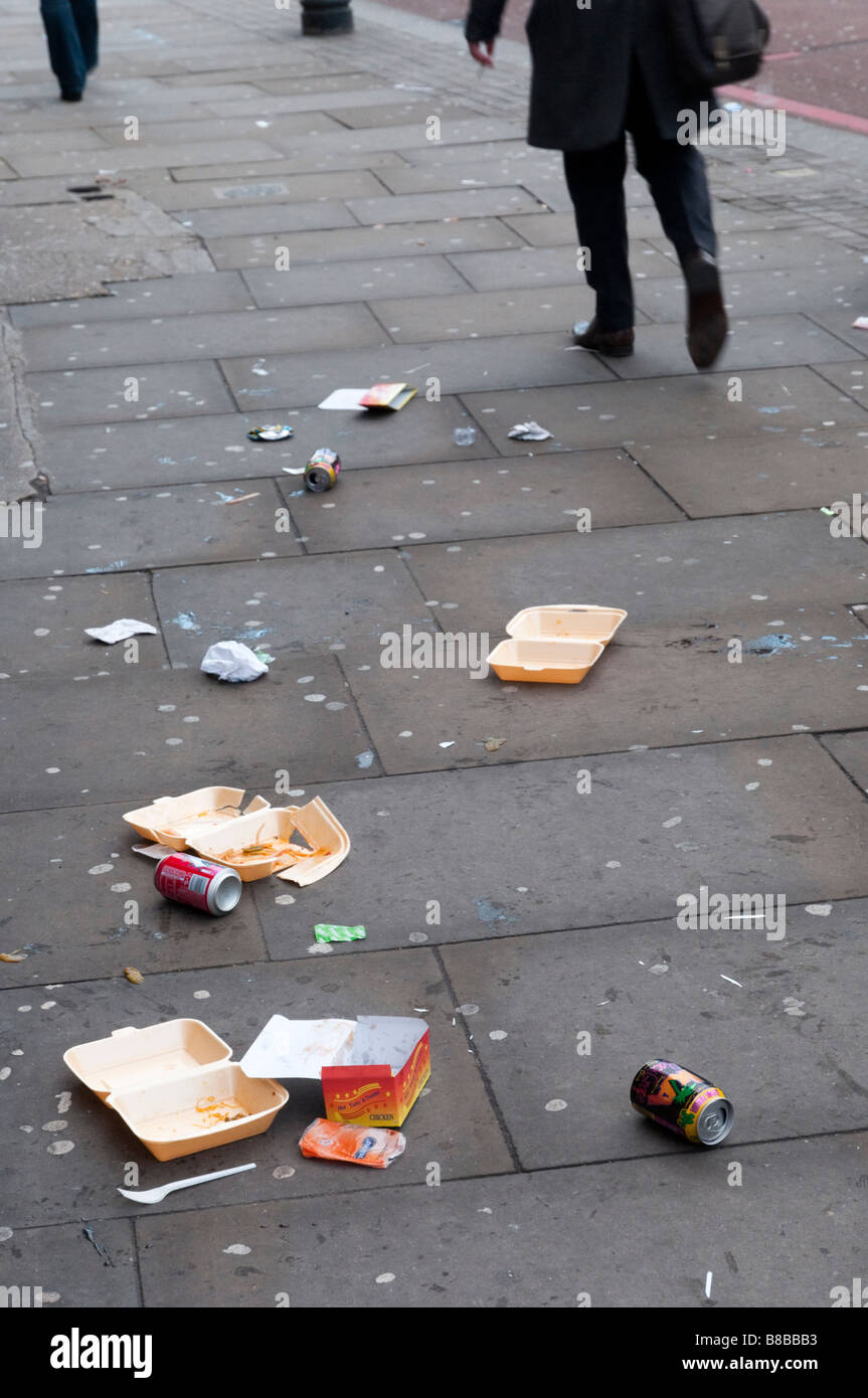 People walking past litter on the pavement, England UK - Stock Image
