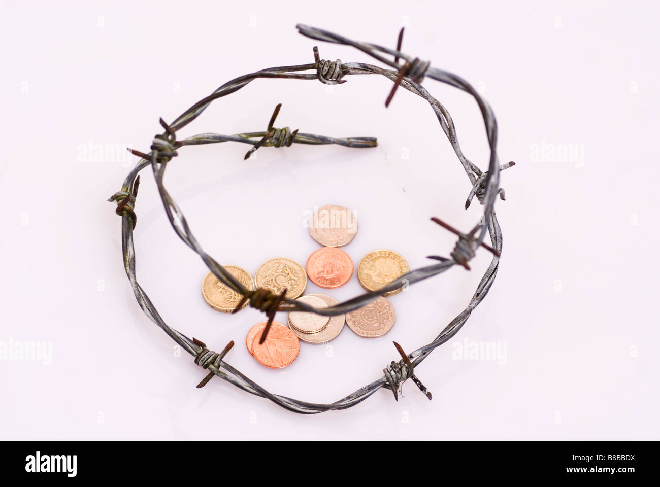Barbed wire around money coins - Stock Image
