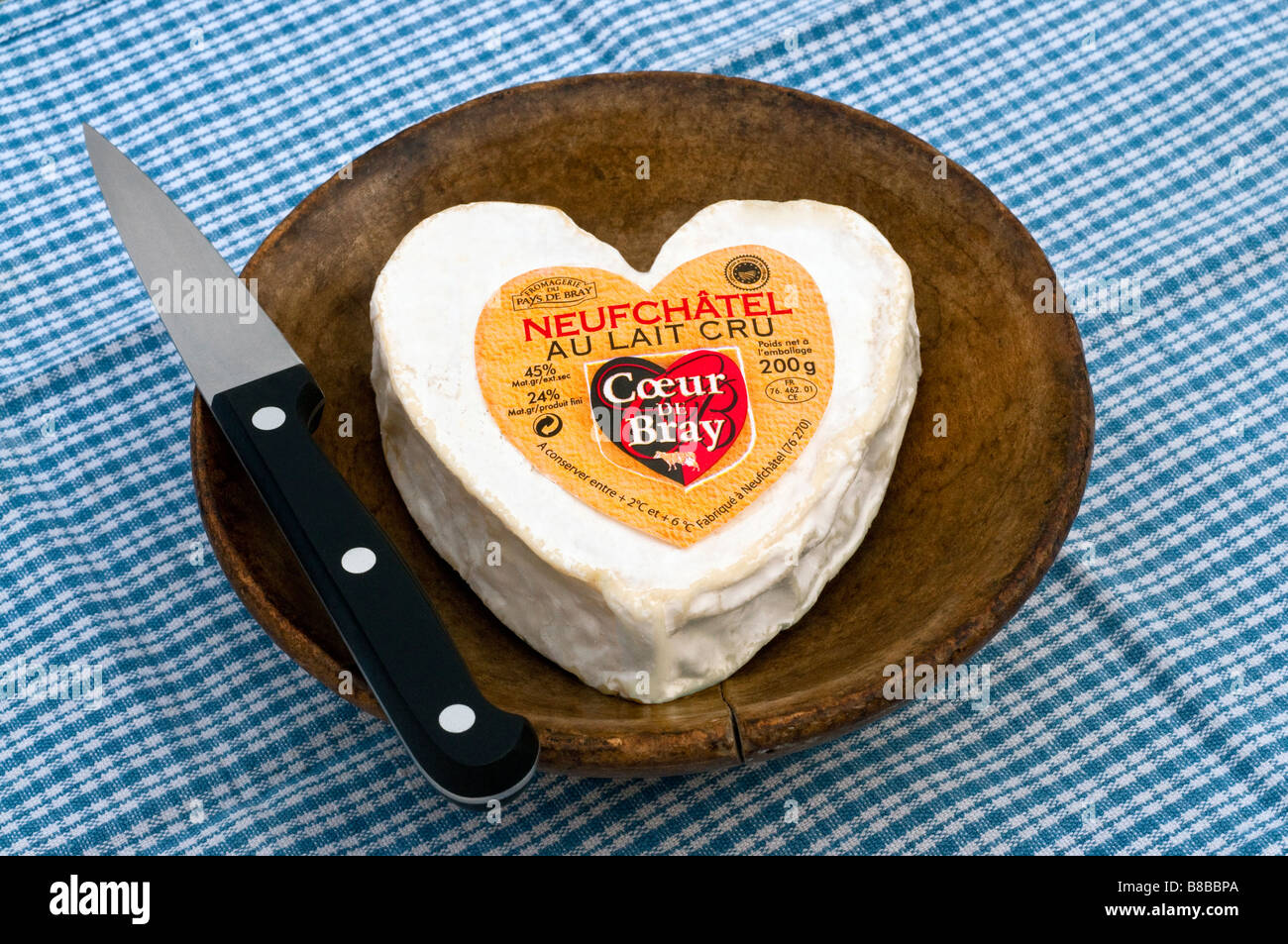 French heart shaped Neufchatel / Normandy fresh soft cheese in old wood bowl - Stock Image
