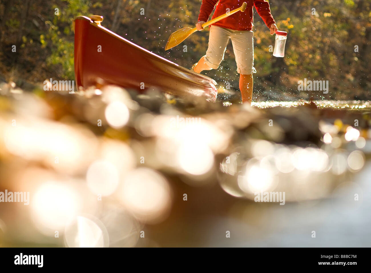 Woman stepping out of canoe in the river - Stock Image