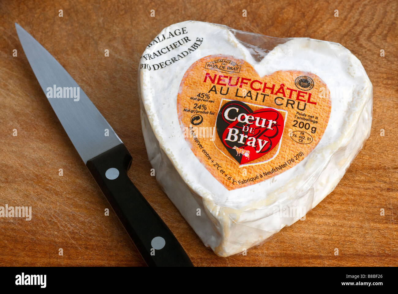 French heart shaped Neufchatel / Normandy fresh soft cheese on wood chopping board. - Stock Image