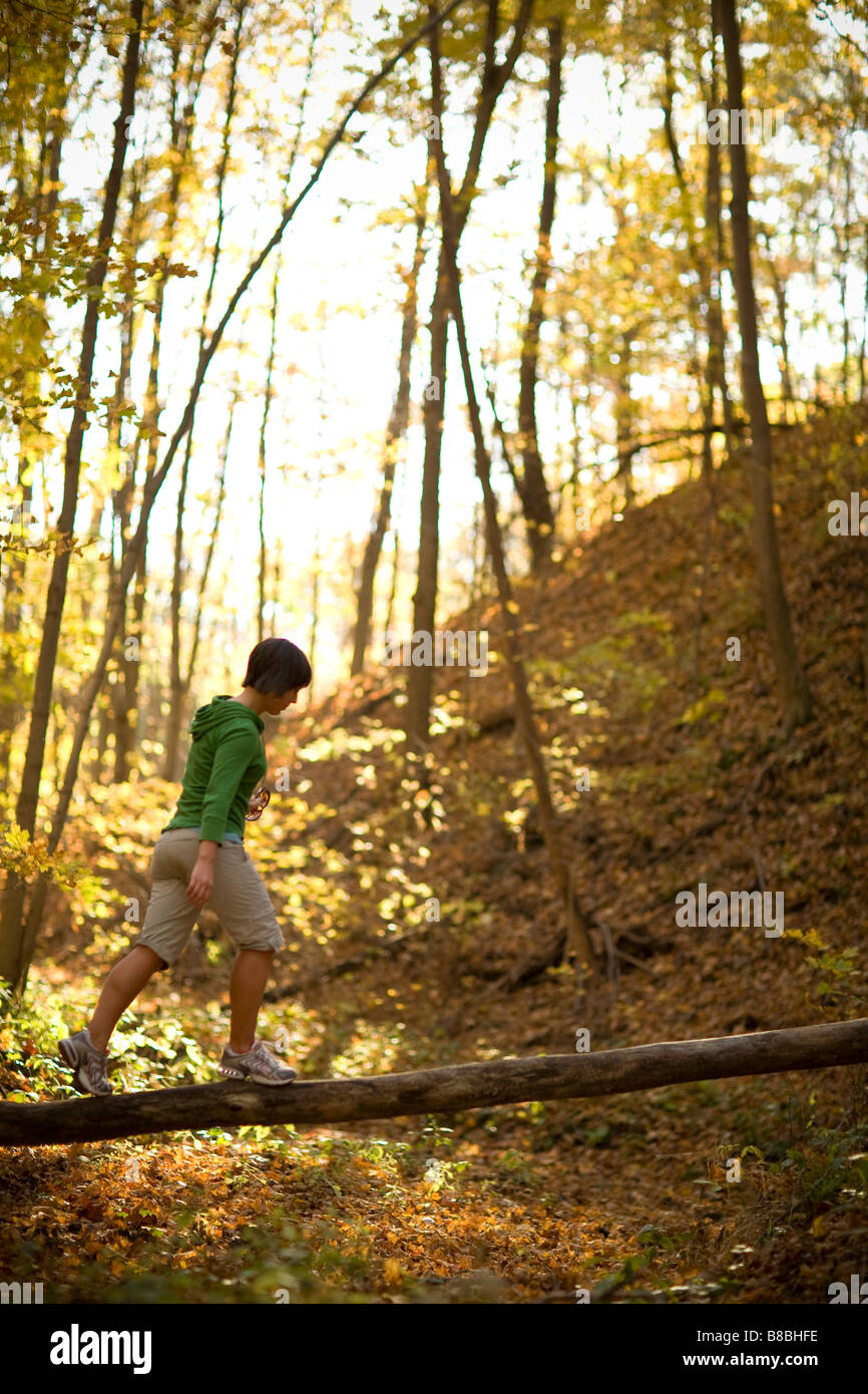 Woman balancing on fallen tree trunk in the woods - Stock Image