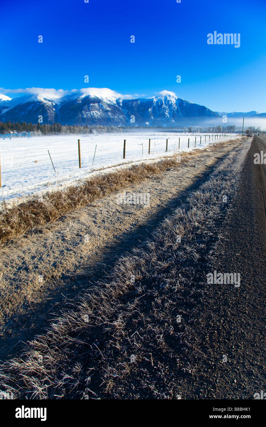 7554af79cba7e Drainage ditch along highway 93 East Kootenay BC Canada with snow covered  mountains in distance and clear blue sky, Canada