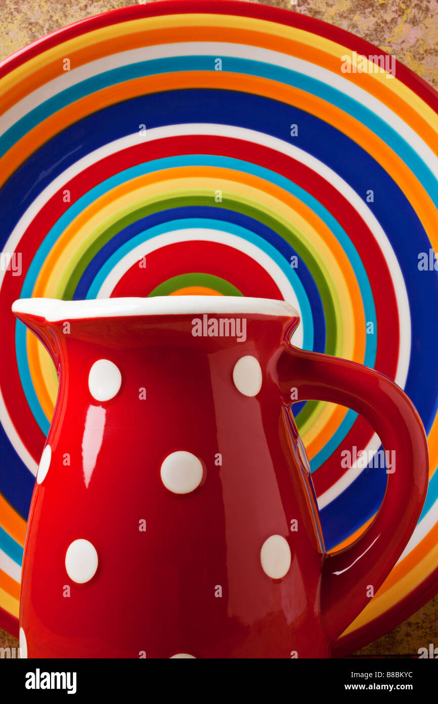 Red pitcher and round plate with circles - Stock Image