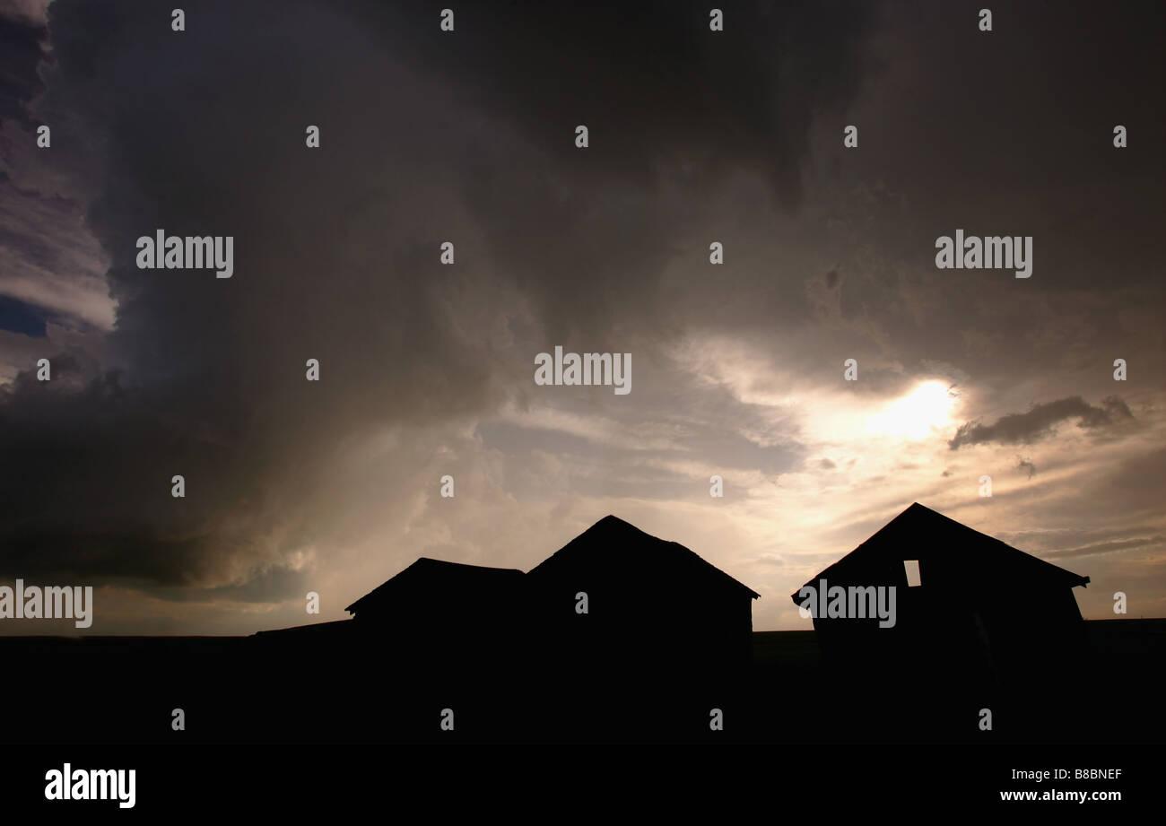 Grain storage bins against storm Clouds, Crossfield, Alberta - Stock Image