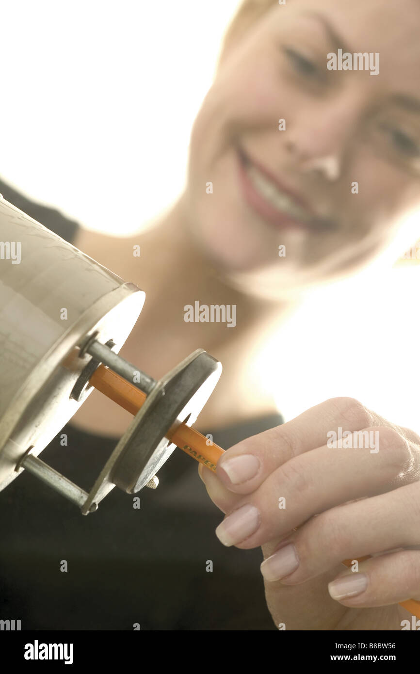 Young Woman Pencil Sharpener - Stock Image