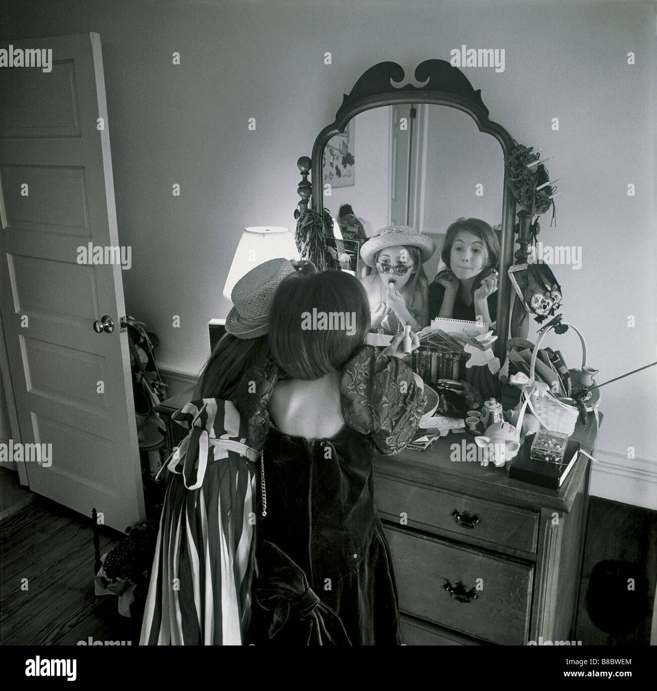 FL4881, Nick Kelsh; Two Young Girls Playing Dress-up   Mirror, BW - Stock Image