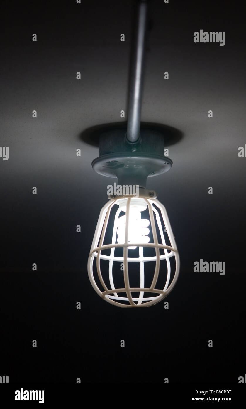 Compact florescent bulb light in a safety fixture - Stock Image